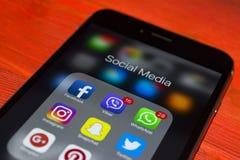 iphone与社会媒介象的7个加号在屏幕上的在红色木桌上 智能手机生活方式智能手机 开始社会媒介 免版税库存照片