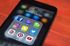 iphone与社会媒介象的7个加号在屏幕上的在红色木桌上 智能手机生活方式智能手机 开始社会媒介a 免版税库存图片