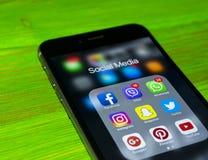 iphone与社会媒介象的7个加号在屏幕上的在绿色木桌上 智能手机生活方式智能手机 开始社会媒介 库存照片