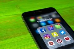 iphone与社会媒介象的7个加号在屏幕上的在绿色木桌上 智能手机生活方式智能手机 开始社会媒介 库存图片
