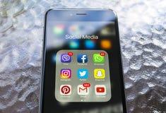 Iphone与社会媒介象的6个加号在屏幕上的在绿色木桌上 智能手机生活方式智能手机 开始社会媒介 免版税库存图片