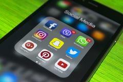 iphone与社会媒介象的7个加号在屏幕上的在蓝色木桌上 智能手机生活方式智能手机 开始社会媒介 免版税库存图片