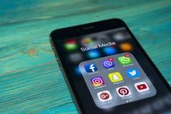 iphone与社会媒介象的7个加号在屏幕上的在蓝色木桌上 智能手机生活方式智能手机 开始社会媒介a 免版税库存照片