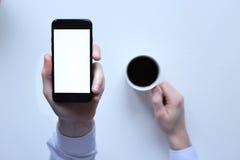 iPhone 7 à disposition sur un fond blanc Cuvette de café blanche Photo stock