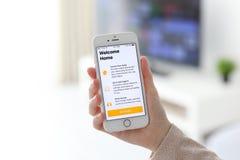 IPhone εκμετάλλευσης χεριών γυναικών με app το σπίτι στην οθόνη Στοκ Φωτογραφίες