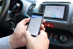 IPhone 6 εκμετάλλευσης ατόμων με τους χάρτες της Apple και το παιχνίδι αυτοκινήτων Στοκ Φωτογραφίες