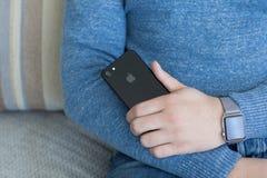 IPhone 7 εκμετάλλευσης ρολογιών της Apple χεριών ατόμων αεριωθούμενο μαύρο Onyx Στοκ Φωτογραφίες