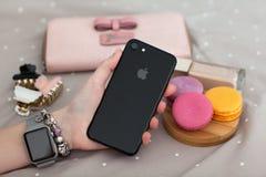 IPhone 7 εκμετάλλευσης ρολογιών της Apple χεριών γυναικών αεριωθούμενο μαύρο Onyx Στοκ φωτογραφία με δικαίωμα ελεύθερης χρήσης