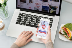 IPhone εκμετάλλευσης χεριών γυναικών με την κοινωνική υπηρεσία Pinterest Διαδικτύου Στοκ Εικόνες