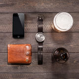 Iphone και της μπύρας κοντά στα ρολόγια σε ξύλινο Στοκ Φωτογραφία