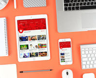 Iphone και ipad πέρα από το κόκκινο υπόβαθρο που επιδεικνύει Youtube app Στοκ φωτογραφία με δικαίωμα ελεύθερης χρήσης