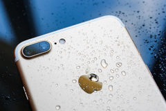 IPhone 7 συν αδιάβροχο με τις πτώσεις βροχής στο οπίσθιο γυαλί backgroud Στοκ Εικόνες