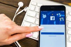 IPhone 7 της Apple με την αρχική σελίδα Facebook στην οθόνη οργάνων ελέγχου στα χέρια γυναικών Αρχική σελίδα facebook COM στο sma Στοκ Εικόνες
