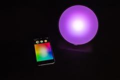 IPhone της Apple που χρησιμοποιείται για να ελέγξει ένα έξυπνο εγχώριο φως χρώματος της Philips Στοκ Φωτογραφίες
