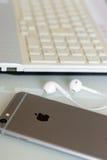 IPhone της Apple στο γραφείο με τα συνδεμένα με καλώδιο ακουστικά Στοκ Φωτογραφίες