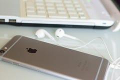 IPhone της Apple στο γραφείο με τα συνδεμένα με καλώδιο ακουστικά Στοκ Φωτογραφία