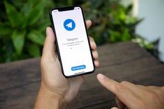IPhone Χ εκμετάλλευσης χεριών ατόμων με την κοινωνική υπηρεσία Telegra δικτύωσης Στοκ Φωτογραφίες