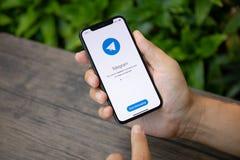IPhone Χ εκμετάλλευσης χεριών ατόμων με την κοινωνική υπηρεσία Telegra δικτύωσης Στοκ φωτογραφίες με δικαίωμα ελεύθερης χρήσης