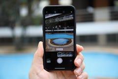 IPhone Χ εκμετάλλευσης χεριών ατόμων με τη κάμερα φωτογραφιών στην οθόνη Στοκ φωτογραφία με δικαίωμα ελεύθερης χρήσης
