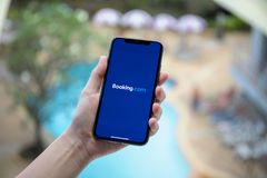 IPhone Χ εκμετάλλευσης χεριών γυναικών κράτηση εφαρμογής σε απευθείας σύνδεση ξενοδοχείο COM Στοκ φωτογραφίες με δικαίωμα ελεύθερης χρήσης