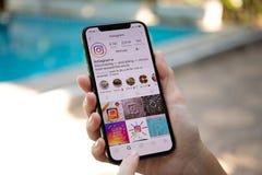 IPhone Χ εκμετάλλευσης χεριών γυναικών με την κοινωνική υπηρεσία Insta δικτύωσης Στοκ Εικόνες