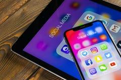 IPhone Χ της Apple και iPad με τα εικονίδια των κοινωνικών μέσων facebook, instagram, πειραχτήρι, snapchat εφαρμογή στην οθόνη Κο Στοκ Εικόνα