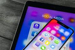 IPhone Χ της Apple και iPad με τα εικονίδια των κοινωνικών μέσων facebook, instagram, πειραχτήρι, snapchat εφαρμογή στην οθόνη Κο Στοκ Εικόνες