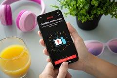IPhone x удерживания женщины с видео- обслуживанием Netflix на экране стоковое фото
