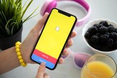 IPhone удерживания женщины с социальным обслуживанием Snapchat сети на экране стоковая фотография