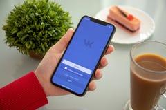 IPhone x удерживания женщины с социальным обслуживанием VK сети стоковые фото