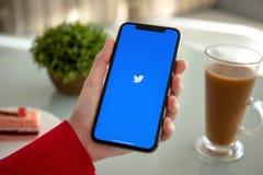 IPhone x удерживания руки женщины с социальным обслуживанием Twitter сети стоковое фото rf