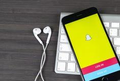 IPhone 7 Яблока с домашней страницей Snapchat на экране монитора Snapchat социальный вебсайт сети Домашняя страница Snapchat com  Стоковая Фотография RF