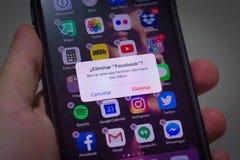 Iphone användare omkring som tar bort Facebook app - spansk version royaltyfri foto