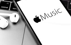 IPhone with Apple Music logo on the screen with Earpods headphones closeup