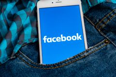 IPhone bianco con il logo dei media sociali Facebook sullo schermo Icona sociale di media fotografie stock