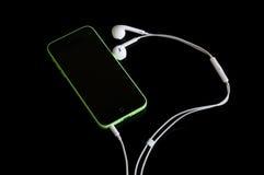 Iphone 5C con le cuffie Immagine Stock