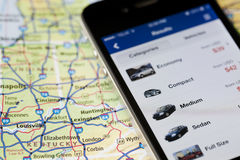 Iphone with car rental application on map of North America. Royalty Free Stock Photo