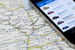 IPhone with car rental application on a map of USA Royalty Free Stock Photo
