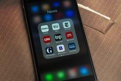 IPhone со значками средств массовой информации: Forbes, времена WSJ, NY, новости CNN, WP, BBC применения, попечитель, Bloomberg и стоковое изображение rf