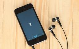 IPhone com logotype de Tumblr em seus tela e fones de ouvido Imagem de Stock Royalty Free