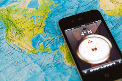 Iphone with compas application on world map Stock Image