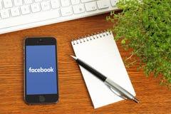 IPhone con il logotype di Facebook sul suo schermo Fotografie Stock