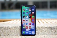 IPhone X con la red social en la pantalla fotografía de archivo libre de regalías
