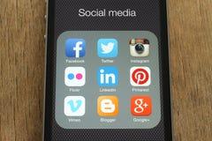 IPhone con los medios iconos sociales populares en su pantalla en fondo de madera Fotos de archivo libres de regalías