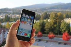 IPhone d'Apple dans la main d'un homme avec le fond de nature Image stock