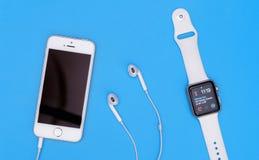 IPhone d'Apple et montre de pomme pour sur le fond bleu Photo libre de droits
