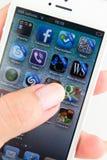 IPhone 5 dans une main d'isolement sur le blanc Image stock