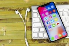 IPhone X de Apple com ícones do facebook social dos meios, instagram, gorjeio, aplicação do snapchat na tela Ícones sociais dos m Fotografia de Stock Royalty Free