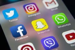 IPhone 7 de Apple con los iconos del medios facebook social, instagram, gorjeo, uso del snapchat en la pantalla Smartphone que co Foto de archivo