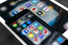 IPhone 7 de Apple e iPad pro com ícones do facebook social dos meios, instagram, gorjeio, aplicação do snapchat na tela Smartphon